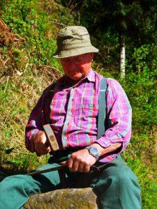 Seniorbauer beim Sense dengeln