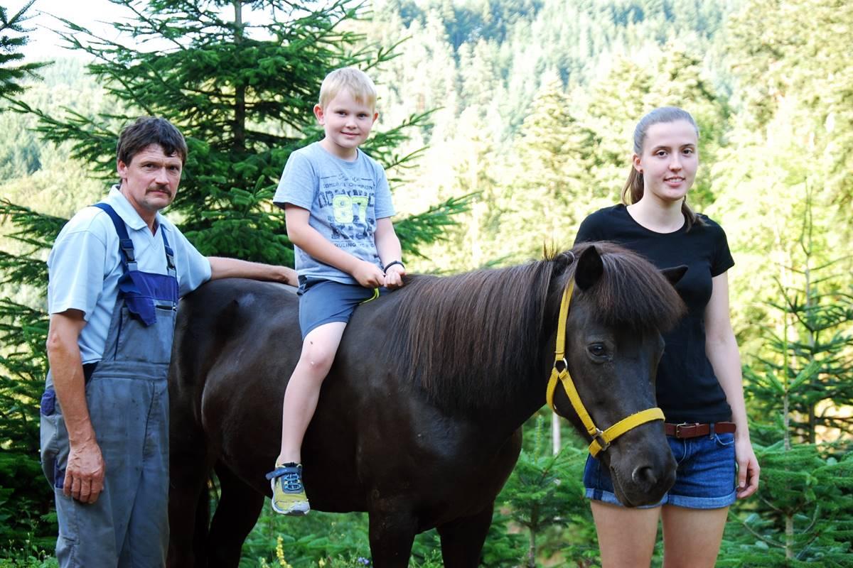 Pony mit kleinem Jungen auf dem Rücken, daneben der Hofbauer und die Tochter vom Halterhof