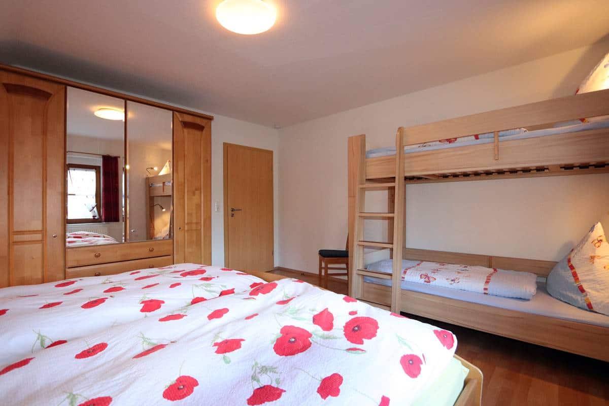 Blick vom Fenster aus über das Doppelbett auf den Kleiderschrank und das Etagenbett