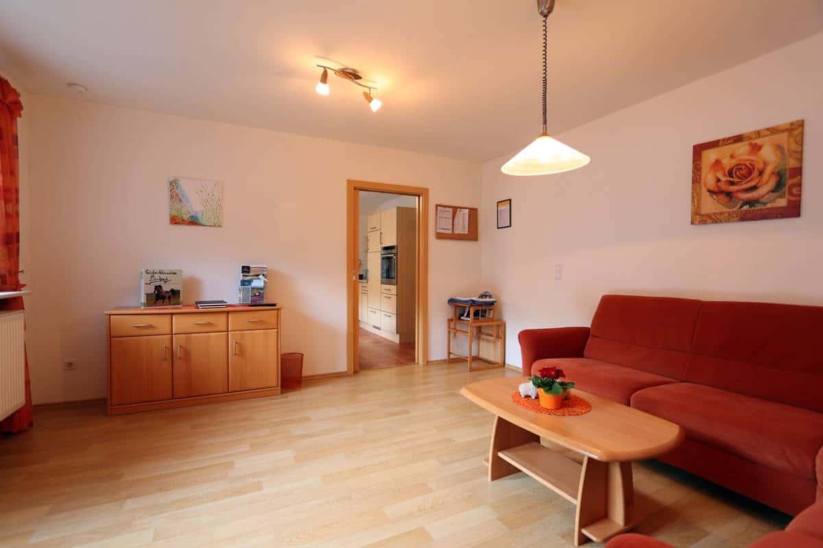 Wohnzimmer mit roter Couchecke und Sideboard mit Büchern und Spielen